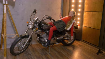 леденец : Young girl lying on motorcycle while photo session in photo studio. Happy teenager girl posing on motorbike at professional photo session. Fashion and modeling