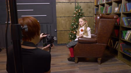 oturum : Baltimore, USA - Desember 25, 2018: girl teenager posing in leather armchair on bookcase and Christmas tree in photo studio. Photograper taking shot of girl model in armchair in New Year photo studio