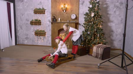 кондитерская : Teenager girls with lollipop posing on sleigh on Christmas tree background. Christmas photo session in photo studio. Backstage girls teenager at professional photo session