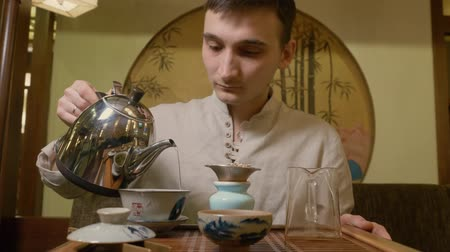 louça de barro : Tea master pouring hot water from kettle to gaiwan for brewing tea at ceremony. Traditional process preparation chinese tea in teaware from yixing clay