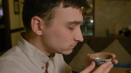 приправленный : Tea lover drinking fresh brewed tea from bowl close up. Young man tasting traditional chinese tea and enjoying original taste, profile view. Tea drinker drinking flavored beverage. Close up