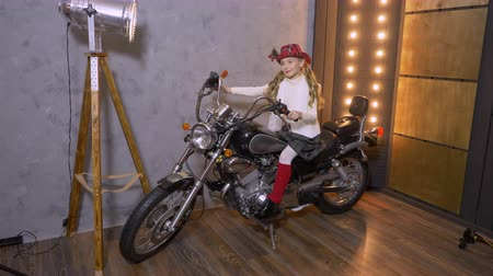 motor vehicle : Studio portrait of pretty young girl in hat sitting on motorcycle in stodio and photographing at lights background