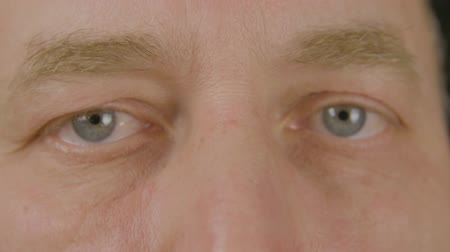 optyk : Man with opened eyes looking and blinking front camera close up. Face adult man winking eye and looking into camera. Macro shooting male eyes. Vision, eyesight, ophthalmology