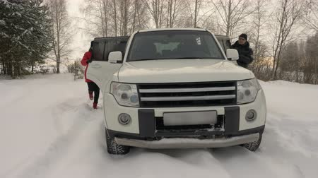 juntar : Family gets in white SUV car standing in snowy winter forest. Mother, father, daughter and son teenager opening car doors and getting inside car parking in winter forest