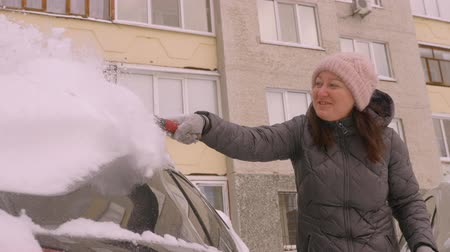 mrożonki : Smiling woman driver cleaning car from snow at parking lot in winter day. Cheerful woman driver using brush for cleaning snow from car in cold snowy winter day Wideo