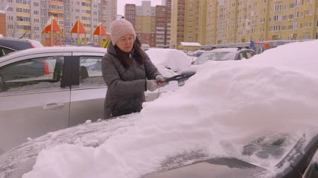 pincel : Young woman driver cleaning snow from car on parking lot in condominium. Auto lady using brush for cleaning snow covered car on parking at winter day Vídeos