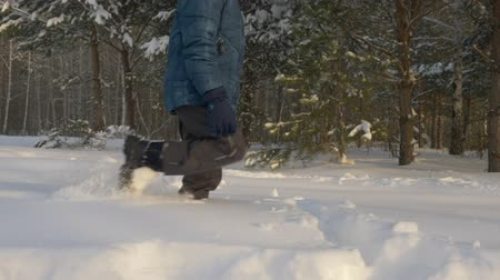 ladin : Happy boy teenager walking through snowdrift in winter forest. Cheerful teenager boy going on snowy forest while winter hiking. Winter activity concept