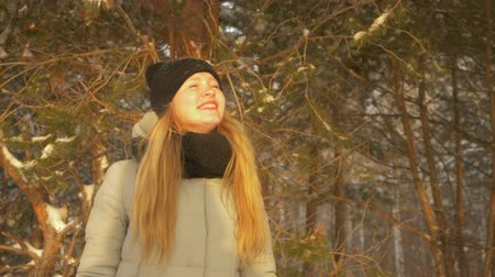 ajustando : Girl enjoying sunny winter day. Close up view beautiful girl laughing and looking on the sun while standing in snowy and frosty winter forest. Slow motion