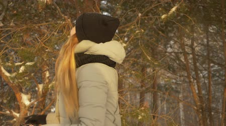 mrożonki : Girl having fun in winter forest. Close up view playful pretty young girl spinning and having fun in cold winter snowy forest. Slow motion Wideo