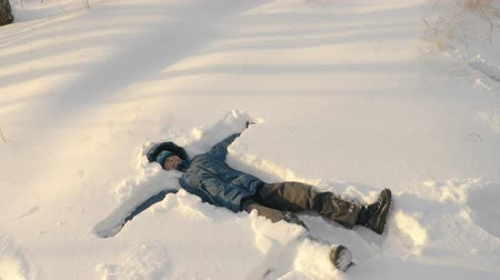 冬 : Teenager making snow angel lying down on snow. Close up view joyful boy in winter clothes making snow angel figure lying down in the snow. Slow Motion overhead top down shot 動画素材