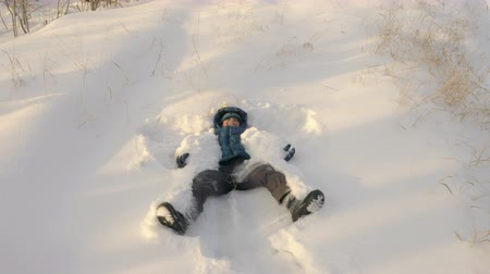 zimní : Little kid making snow angel lying down on snow. Front view joyful boy in winter clothes making snow angel figure lying down in the snow. Slow Motion overhead Dostupné videozáznamy