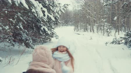 vakáció : Girl running to hug her mother. Teenage girl runs to meet mother in the snowy forest. Mother and daughter hugging in the snowy and frosty woods. Slow motion