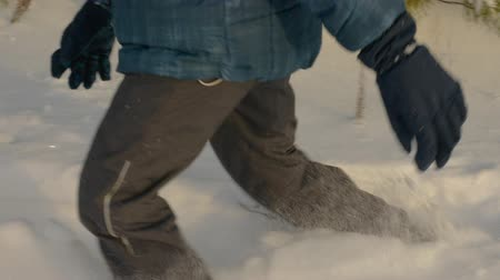 felicidade : Teenage boy walking and falling into snow. Side view playful little kid legs having fun in snowy park. Travel concept. Slow Motion