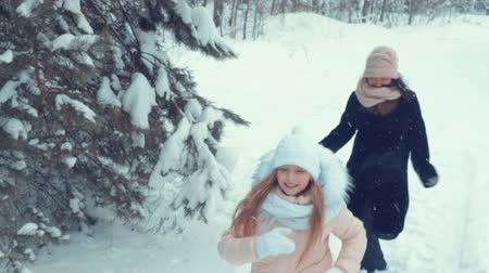 lanscape : Girl and woman run through the snowy forest. Playful little girl, daughter running away from her mother. Joyful mother and daughter having fun in the winter woods. Slow Motion