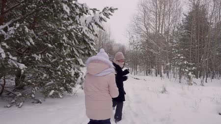 lanscape : Small girl running after a woman. Little daughter tries to catch up with mother, while running through snowy forest path way. Slow Motion