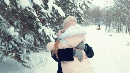lanscape : Mother and daughter run towards each other. Little girl and happy woman run and hug each other tightly. Mom and daughter are happy to meet in the snowy woods. Slow Motion Stock Footage