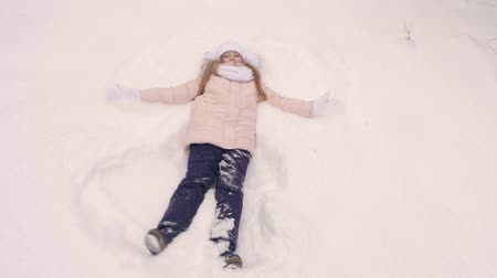 vállkendő : Girl making snow angel. Overhead view playful teenage girl shows snow angel while fall down on a the snow. Slow motion