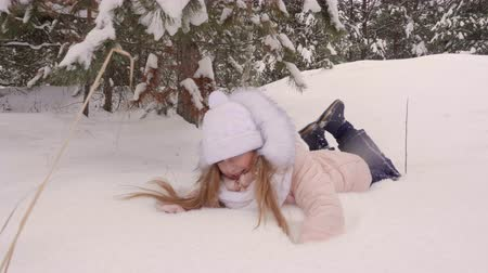 executar : Girl running and falling down on snow. Adorable little girl having fun in snowy winter forest pine trees woods. Slow Motion Stock Footage