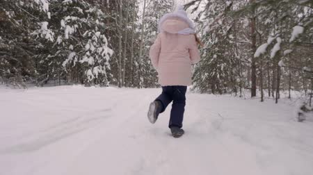 arka görünüm : Teenage girl running through snowy forest. Back view running playful girl among snowy pine trees. Teenager in the frosty snowy woods. Slow motion Stok Video