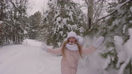 xale : Girl hitting snow from the pine trees branches. Front view running girl through winter path with snowy pine trees aside. Little girl touching pine trees branches with snow. Slow motion.