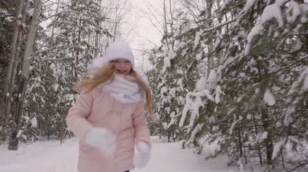 flee : Girl running in the snowy woods. Front view joyful teenage girl running through winter forest. Slow Motion