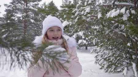 parkland : Little girl drinking hot tea in winter forest. Close up cute teenage girl with a cup of hot drink in hands, girl drinking tea and enjoying snowfall in frosty woods among snowy pine trees. Slow Motion