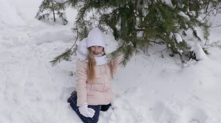 harikalar diyarı : Teenage girl sitting under snow pine tree. Happy girl having fun in winter woods, while playing with snowy pine tree branch. Slow Motion