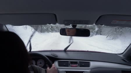 arka görünüm : Woman driving on winter forest offroad. Adult female driver in snowy woods path among pine trees. POV