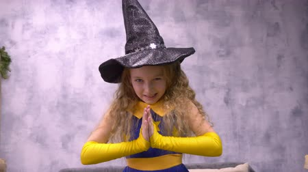 hag : Stargazer girl rubs hands. Close up front view little witch viciously rubs her hands, ready to cast a spell wizard Helloween hat. Wish warlock close up front view