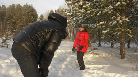 volný čas : Couple man and woman throwing snowballs while winter walk in snowy forest. Happy man and woman in love playing in snowballs at winter walk in coniferous forest. Winter people activity