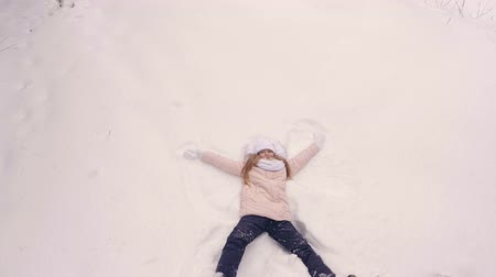 volný čas : Happy girl teenager falling on snow and flying like snow angel view from above. Cheerful girl teenager enjoying snowy weather and lying on snow like winter angel. Copy space background