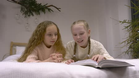 mentiras : Two girls reading a book. Cute teenage girls lies on bedand reading a book while lying on the bed in the room. Education concept