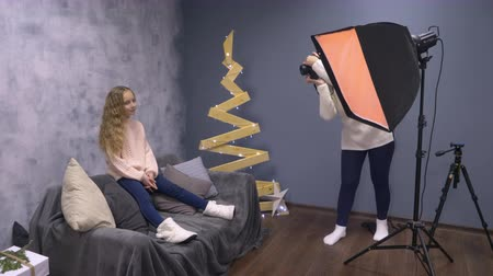 warsztat : Photographer shooting little girl. Side view female photographer, woman, shooting teenage girl in the studio with decorative Christmas tree Wideo
