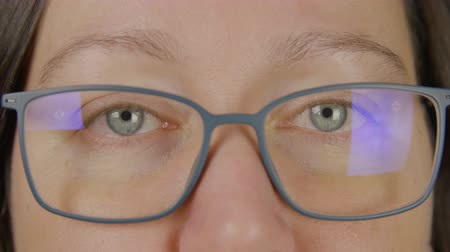 sighted : Portrait woman wearing eyeglasses blue eyes close and open, wink, macro studio shot close up face
