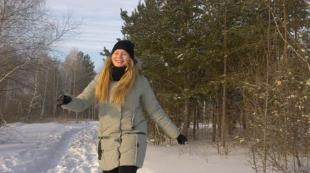 flee : Young Beautiful Caucasian Girl Woman Dressed In Jacket walks and jump Playing In Winter Forest In Snowy Day. Playfull girl funny front view