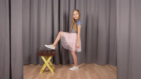 küçük kız : Young model girl posing in studio. Front view, caucasian beautiful teenage model girl posing in different ways in front of camera with a chair aside. Photoposing concept Stok Video
