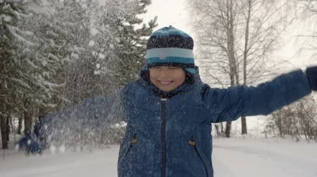 incidence : Teenager boy blow snow from hands in winter wood forest park. Caucasian boe fell down. Falling snow angel. Funny happy guy throw snow and falling down Stock Footage