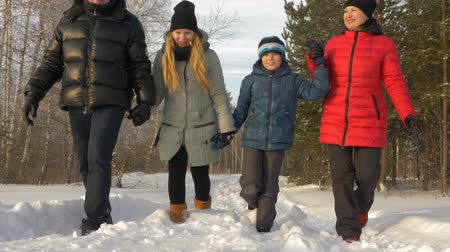 filha : Friendly family walking through winter park by snow path sunny day. Natural day light track shot front view. Winter vacation happy family rest in park snowy pine tree forest Vídeos