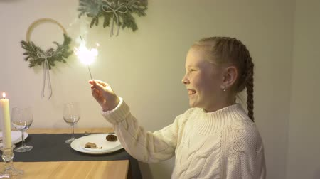 égés : Smiling girl teenager holding in hand bright sparkler sitting at Christmas table. Happy girl looking on bengal light in hand while celebrating Christmas holiday