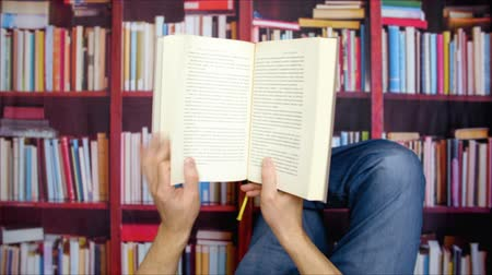издательский : Man holding in hands book and reading lying in university library on bookcase background. Unrecognizable man reading textbook in home library Стоковые видеозаписи