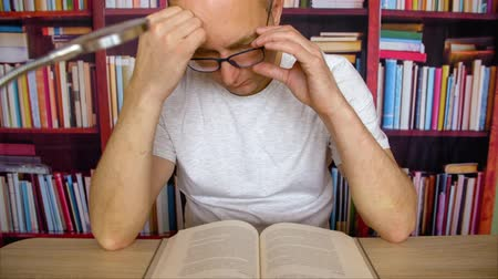 публиковать : Focused man in glasses reading book sitting at table with lamp in home library. Concentrated man student reading textbook in university library before exam on bookcase background Стоковые видеозаписи