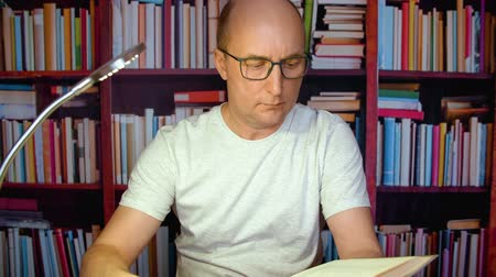 публиковать : Adult man reading interesting encyclopedia in scientific library on bookcase background. Handsome man in glasses reading book at table with lamp in evening library. Read and brainstorm concept Стоковые видеозаписи