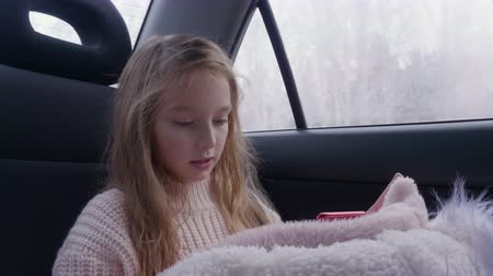 kürk : Cute young girl with long hair drive travel in car and use smart phone. White girl in pink warm sweater looking cell phone gadget. White fur jacket winter travel