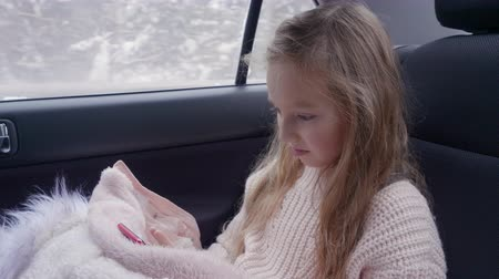 lugares sentados : Young adorable girl surf internet while travel in back sits car at smartphone. Winter travel vacation. White caucasian girl with long hair. Read information on cell phone. Travel concept Stock Footage