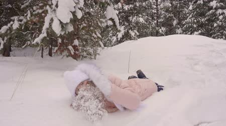 xale : Funny joyful white girl walk by snowy pine tree woods dancing and fall to white snow. Caucasian girl lies on snow winter. White fur long hair pink coral jacket. Winter clothes. Knitted hat and scarf.