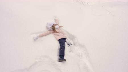 szron : Young girl in coral pink jacket walk and fall to snow than show snow angel butterfly movement of legs and hands overhead view top to down snowfall play. Slow motion. Girl lies at white snow