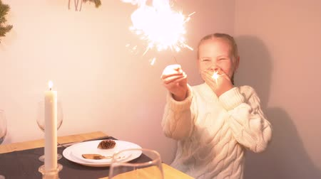 Бенгалия : Young white teenager girl set on fire burn bright sparkler from christmas candle and laugh smile joyful. Girl in white knitted sweater at christmas table hapy birthday Стоковые видеозаписи