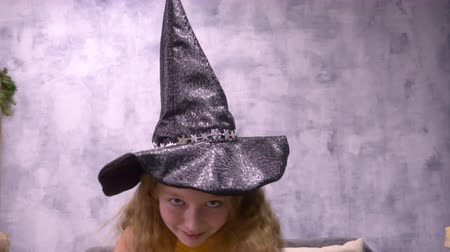 astrologer : Sly witch astrologer rubs his hands greedily looking into the camera. Young teenage white girl halloween costume with long hair. Close up portrait stargazer girl at abstract background. Halloween hat