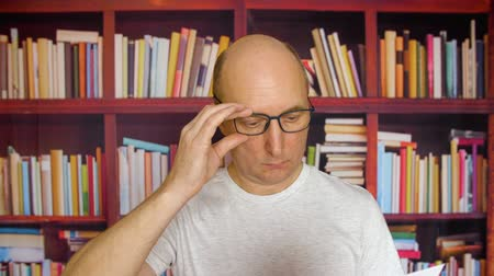 кавказский : Business Man reading paper documents. Close up view confident man in eyeglasses reading paper documents standing in front of book shelves. Man reading in library Стоковые видеозаписи