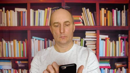 higher : Man using smartphone in library. Satisfied man with eyeglasses texting on smartphone, while standing in front of bookshelves. Close up view man with cell phone.